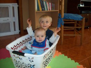 "Two year old, Jared, and 9-month-old, Luke enjoy a ""ride"" in the basket mobile."